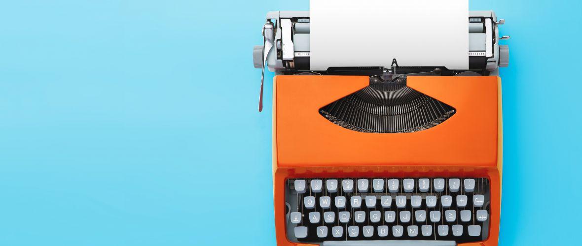 Old orange typewriter on blue background